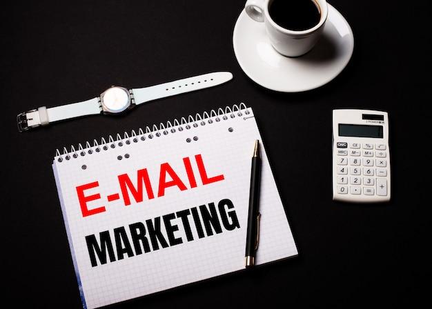 Kaffee in einer weißen tasse, eine armbanduhr und ein taschenrechner auf einem schwarzen tisch. in der nähe ist ein stift und ein notizbuch mit dem text e-mail marketing