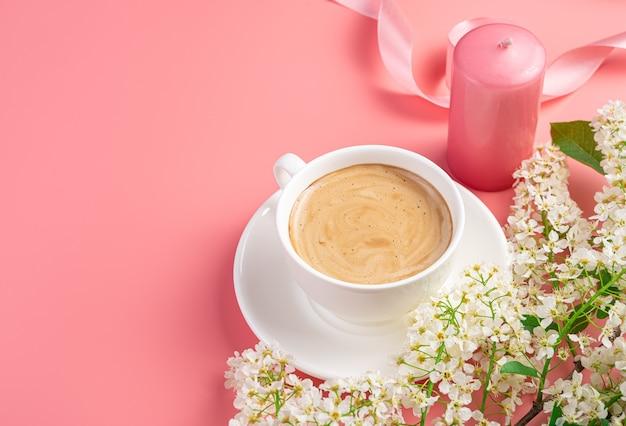 Kaffee in einer weißen tasse kerze und blumen auf rosa hintergrund mit platz zum kopieren