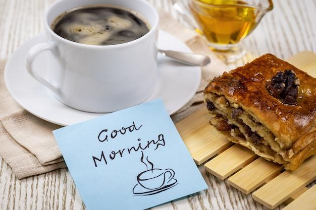 Kaffee in einer weißen tasse mit einem blätterteig aus honig und walnüssen und einem aufkleber