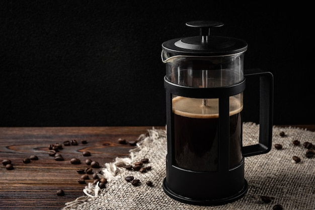 Kaffee in französischer presse und kaffeebohnen auf dunklem holzhintergrund.