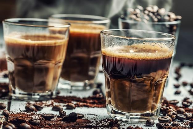 Kaffee in glastassen gemischt mit sahne und bestreuten kaffeebohnen.