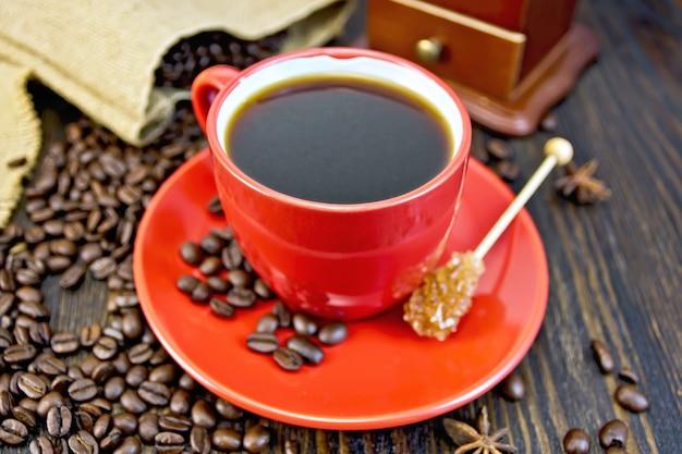 Kaffee in roter tasse zucker, eine tüte kaffeebohnen, sternanis und kaffeemühle auf dem hintergrund von holzbrettern