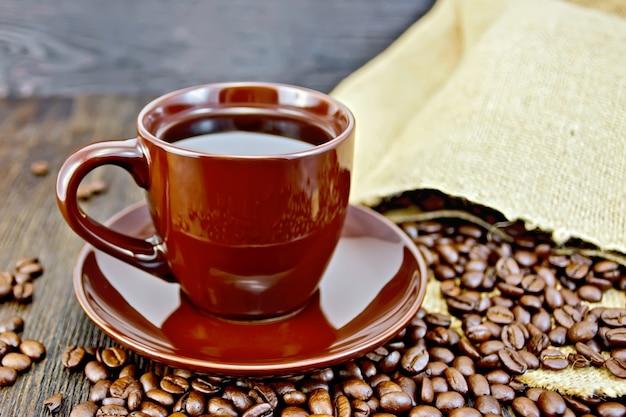 Kaffee in tasse braun, eine tüte kaffeebohnen auf dunklem holzbretthintergrund