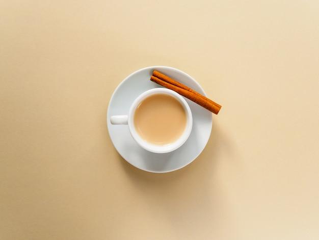 Kaffee in weißen tassen und zimtstangen auf einem gelben.