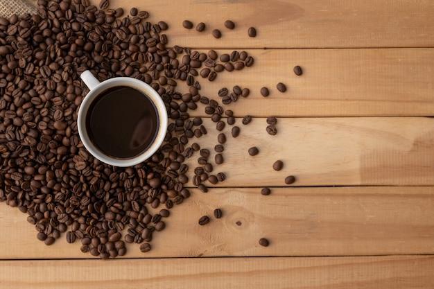 Kaffee in weißer tasse mit bohnen auf holztisch