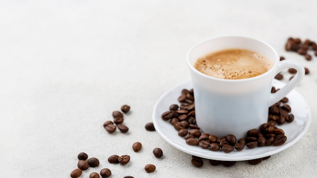 Kaffee in weißer tasse mit bohnen auf teller