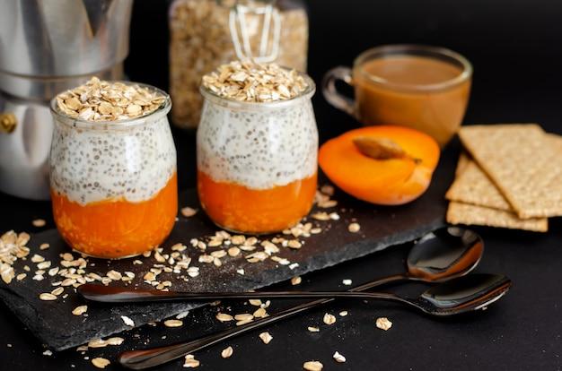 Kaffee, joghurt-chia-pudding mit frischer aprikose und hafer blättert zum frühstück auf schwarzem ab