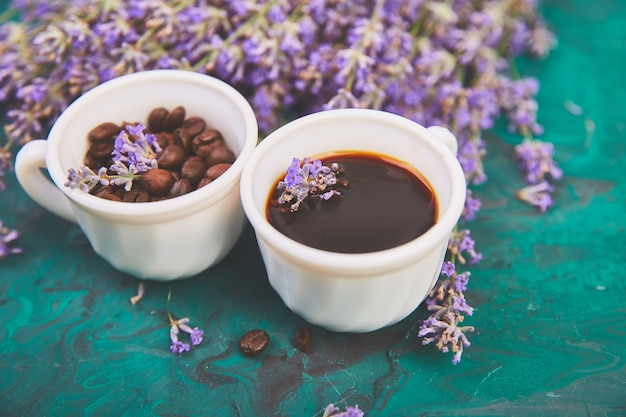 Kaffee, kaffeebohnen in den schalen und lavendel blühen auf grünem hintergrund