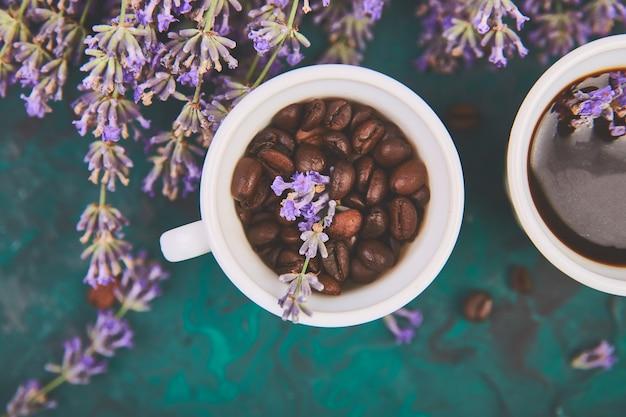 Kaffee, kaffeekorn in tassen und lavendelblüte auf grünem tisch von oben. guten morgen konzept. frauenarbeitsplatz. gemütliches frühstück. attrappe, lehrmodell, simulation. flacher laienstil