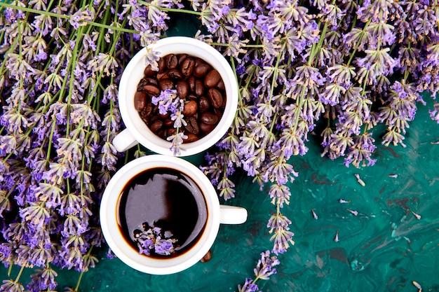 Kaffee, kaffeekorn in tassen und lavendelblume auf grünem hintergrund