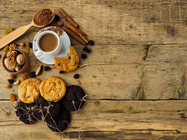 Kaffee, kekse und nüsse auf einem holztisch. platz für text auf dem tisch.