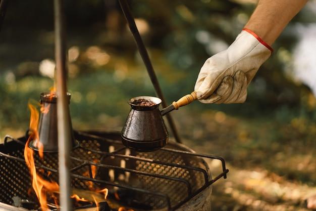 Kaffee kochen auf dem scheiterhaufen kaffee oder tee auf dem feuer der naturtouristenausrüstung zubereiten
