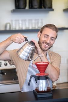 Kaffee kochen. lächelnder mann in einer schürze, die im café steht und wasser in übergießen von der teekanne gießt, die kaffee macht