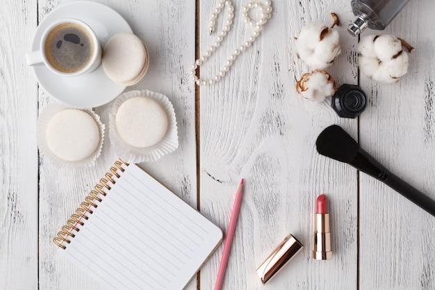 Kaffee, kuchen macaron, sauberes notizbuch, brille und blume auf rosa tisch von oben.