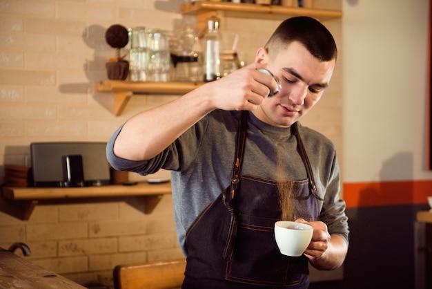 Kaffee latte barista, der muster in einer tasse kaffeestube macht.