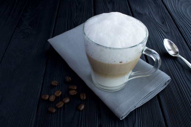 Kaffee latte in der glasschale auf dem schwarzen hölzernen hintergrund. nahansicht. speicherplatz kopieren.
