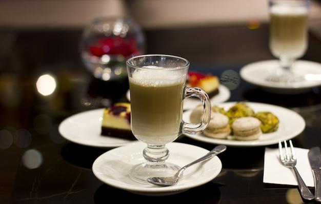 Kaffee latte in einem glas mit dem silbernen löffel und gebäck