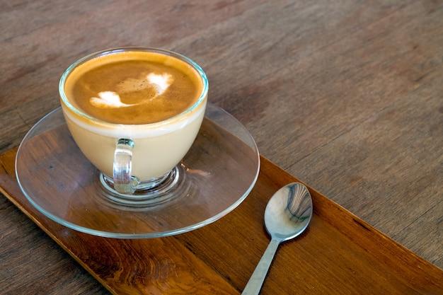 Kaffee latte kunst im café, auf holz tisch.