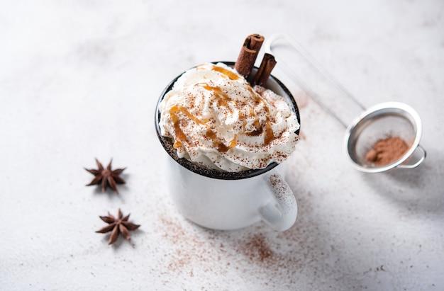 Kaffee latte mit cremiger karamellcreme und zimt in einem weißen becher auf einem weißen tisch. makroansicht und speicherplatz kopieren