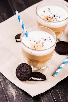 Kaffee latte mit schokoladenplätzchen über schwarzem hölzernem hintergrund.