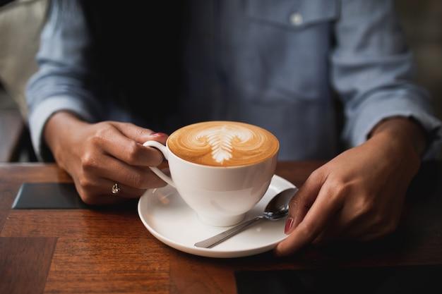 Kaffee lattekunst im café mit der frauenhand
