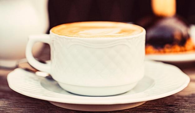 Kaffee lieben. tasse frischer cappuccino. cappuccino in einer tasse, heißer latte, leckerer kaffee. zeit für kaffee. kaffee trinken. kaffee oder kaffeetasse am morgen im café.