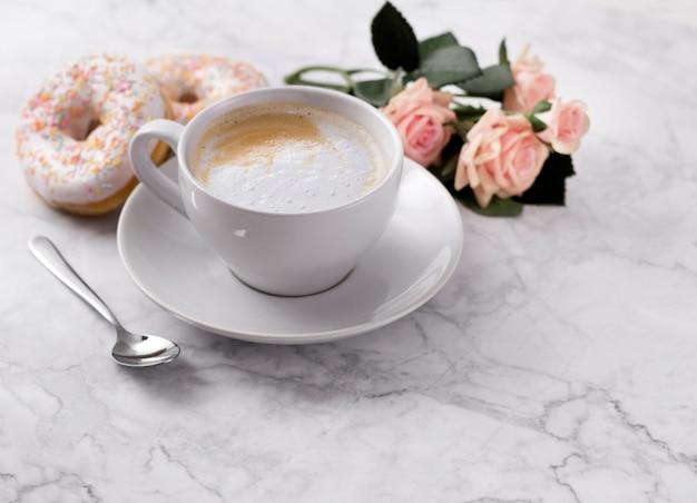 Kaffee mit buntem donut im weißen marmor