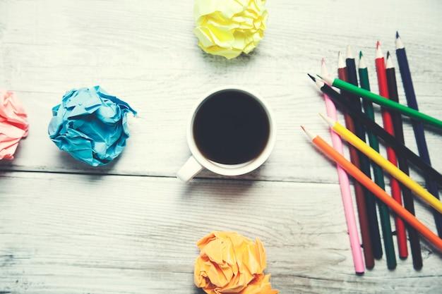 Kaffee mit bunten stiften und papieren