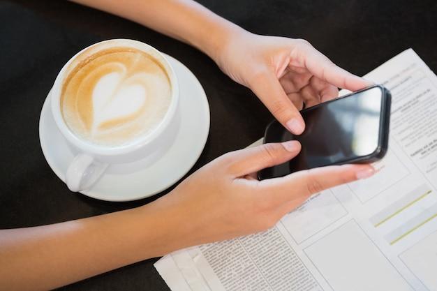 Kaffee mit einem herzen und händen, die ein telefon halten