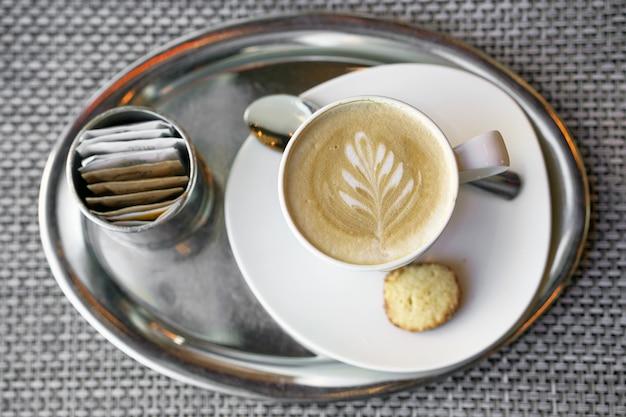 Kaffee mit einem muster auf dem schaum. draufsicht auf einen hellbraunen schaum, ein muster aus milchschaum in form eines blattes.