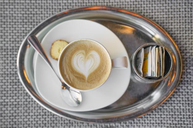 Kaffee mit einem muster auf dem schaum. draufsicht auf einen hellbraunen schaum, ein muster aus milchschaum in form eines herzens.