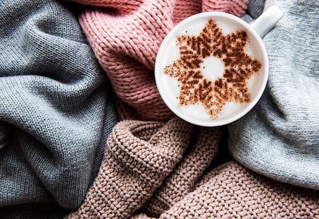 Kaffee mit einem schneeflockenmuster auf einer warmen strickpulloveroberfläche