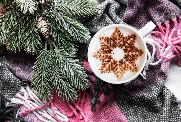 Kaffee mit einem schneeflockenmuster auf einer warmen wollplaidoberfläche