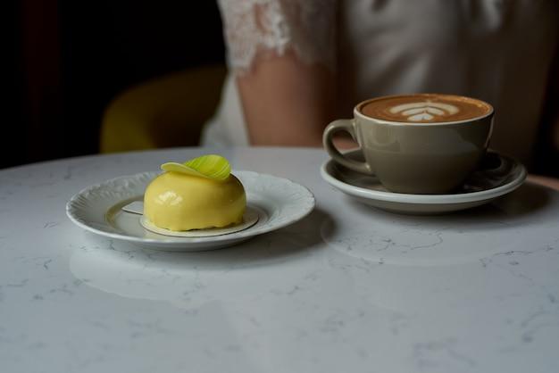 Kaffee mit gebäck. tasse kaffee und mousse-kuchen im trendigen café-stil. kuchen mit einer tasse cappuccino. perfektes frühstück in einem modernen café.