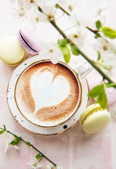 Kaffee mit herzförmigem muster und süße makronen-desserts auf einer rosa fliesenoberfläche