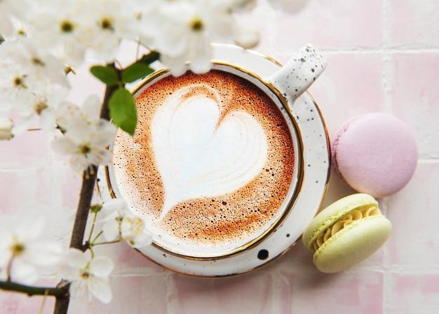 Kaffee mit herzförmigem muster und süßen makronen-desserts auf rosa kachelhintergrund