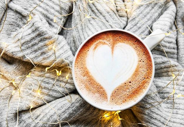 Kaffee mit herzmuster auf einer warmen strickpulloveroberfläche