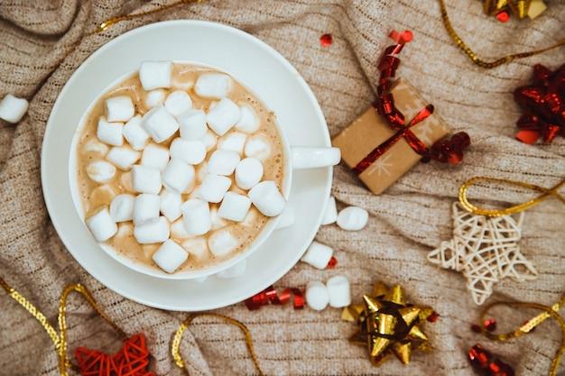 Kaffee mit marshmallows auf einem hintergrund des strickstoffs mit geschenken und feiertagsschleifen
