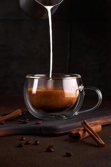 Kaffee mit milch im glas auf dunklem hintergrund. hand, die milchcreme in kaltem kaffee gießt. konzept des leckeren erfrischungsgetränks mit kaffee. kopieren sie platz für text, menü oder rezept