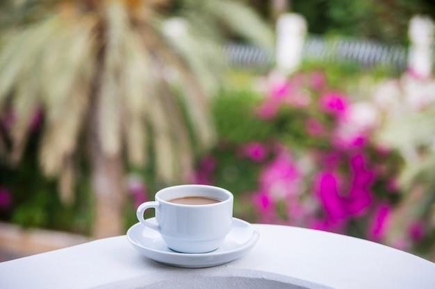 Kaffee mit milch in einer weißen tasse auf dem balkon des hotels.
