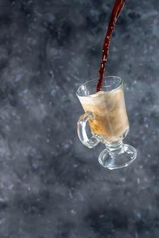 Kaffee mit milch und keksen in herzform. der prozess des eingießens von kaffee in ein glas milch. levitation.