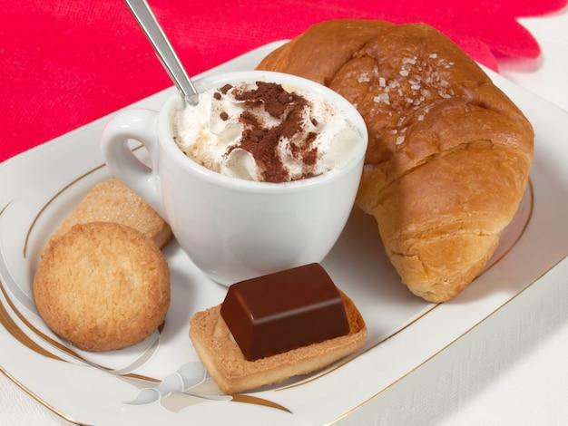 Kaffee mit sahne und kakaopulver und croissant