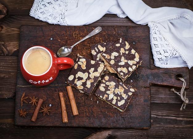 Kaffee mit schaum in einem roten keramikbecher auf dem küchenschneidebrett