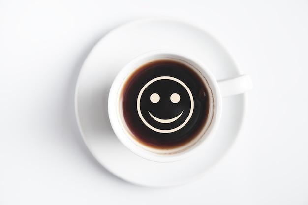 Kaffee mit smiley auf weißem schreibtisch.