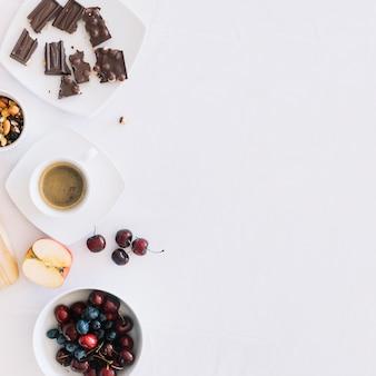 Kaffee mit trockenfrüchten; schokoladenstücke und früchte auf weißem hintergrund