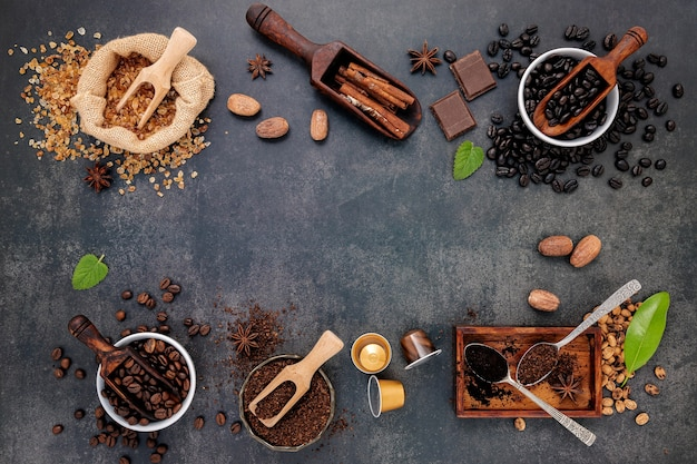 Kaffee mit verschiedenen gerösteten kaffeebohnen und geschmackvollen zutaten für eine leckere kaffeezubereitung auf dunklem stein.