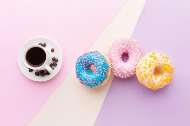 Kaffee nahe bei gesetzter draufsicht des donuts