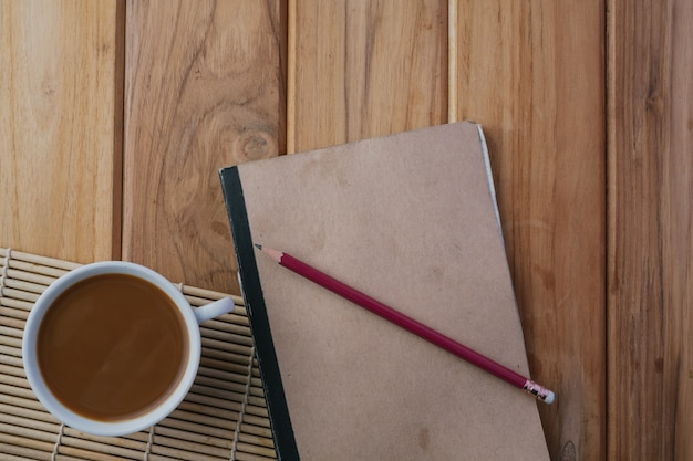 Kaffee neben dem buch auf dem braunen holzboden.