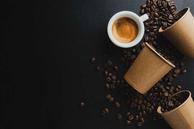 Kaffee- oder null-abfall-konzept. kaffeebohnen in pappbecher mit tasse espresso auf dunklem hintergrund.