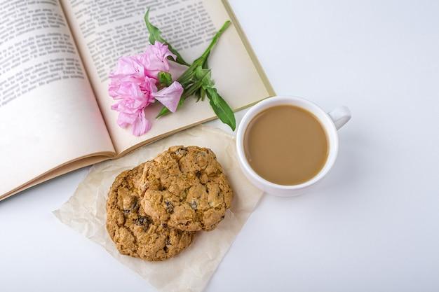 Kaffee oder tee mit milch und haferkeksen. lesen des alten buches und des snacks im frühling, sommertag im garten